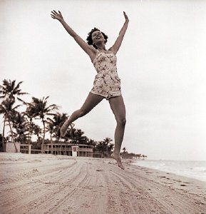 girl-leaping-into-air-at-beach
