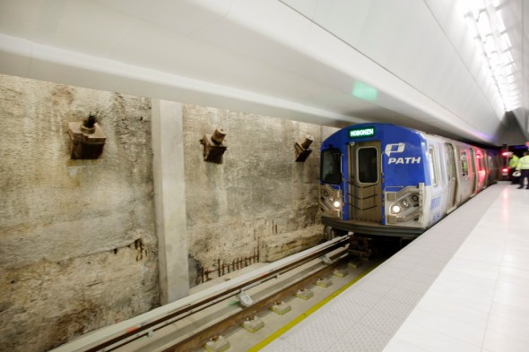 A PATH train passes the slurry wall as it enters the newly-opened section of the World Trade Center PATH station, Tuesday, Feb. 25, 2014, in New York. The slurry wall remains from the original World Trade Center construction of the 1970's, when it was installed to withstand water pressure from the Hudson River on the site. (AP Photo/Mark Lennihan)