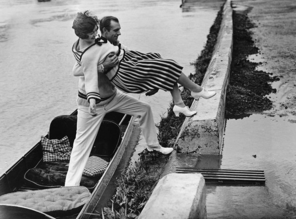 1925: A chivalrous gentleman helps his lady friend onto the towpath from a punt at Richmond,