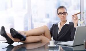 Hot businesswoman sitting with high heels feet up on office desk, holding cigar, looking at camera confidently.