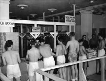 A line of underwear-clad draftees wait in line to check their clothes at an unidentified military facility, August 1944. (Photo by FPG/Getty Images)