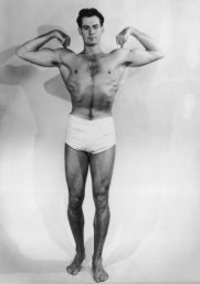 A muscular young man flexes his biceps, circa 1930. (Photo by FPG/Hulton Archive/Getty Images)