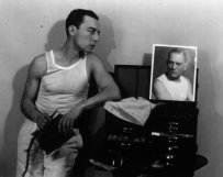American comic actor Buster Keaton (1895 - 1966) originally Joseph Francis Keaton, engages in a staring match with a photograph of Lon Chaney as he prepares to apply his make-up. (Photo by Ruth Harriet Louise/Getty Images)
