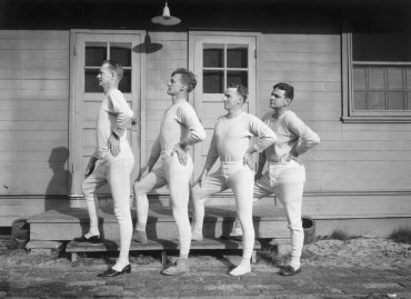 circa 1915: Four men wearing long underwear pose in a profile lineup in front of a wooden barrack. (Photo by Hulton Archive/Getty Images)